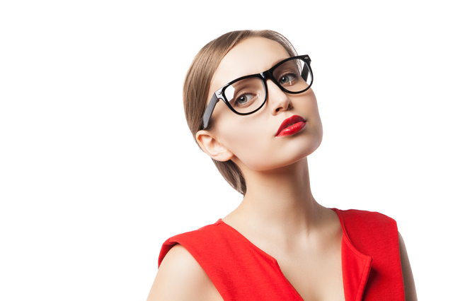 Portrait of woman in glasses and red dress looking away