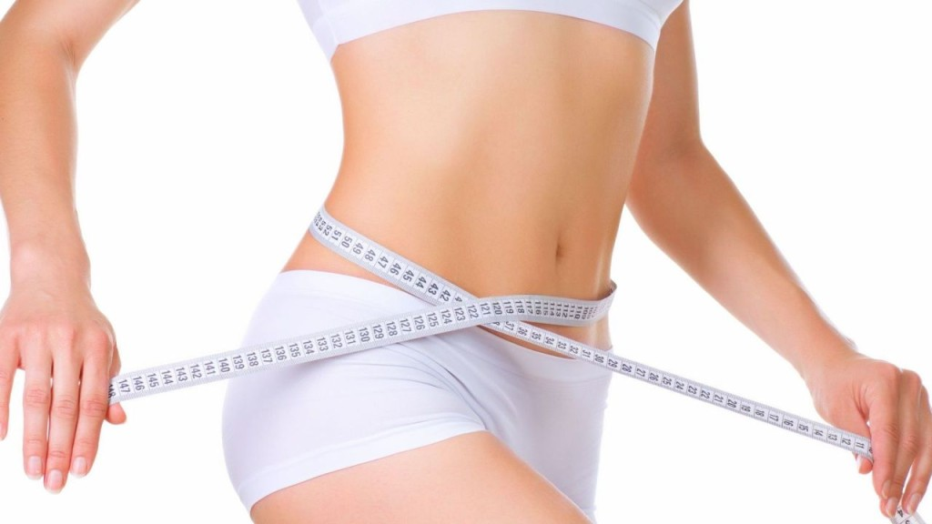 14649207 - woman measuring her waistline  perfect slim body